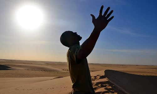 Man experiencing the freedom of the Sahara Desert as the sun looms above his head. Sir Driver Tours. Private tour.